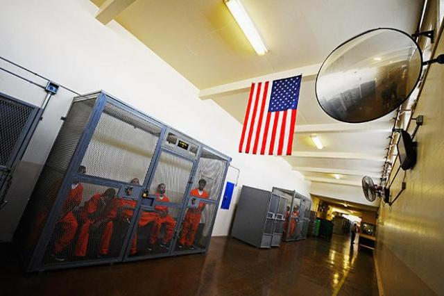 Inmates at Chino State Prison sit inside a metal cage in the hallway on December 10, 2010, in Chino, California. © 2010 Kevork Djansezian/Getty Images